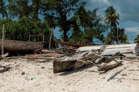 wooden handmade boat with mast on fishing village shore in Zanzibar