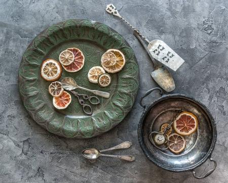 Photo pour Morceaux d'oranges séchées dans des plats vintage sur un fond de béton gris - image libre de droit