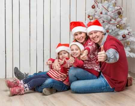 big family in santa hats near the christmas tree