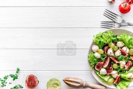 Photo pour Salade aux figues, mozzarella et raisins sur fond de bois blanc. Vue du dessus, espace de copie - image libre de droit