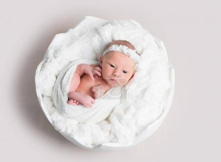 Vista superior de la niña recién nacida acostada en un tazón