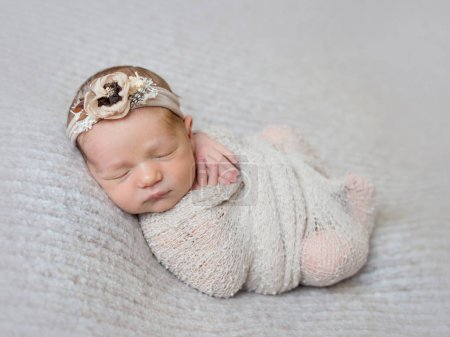 Newborn baby girl swaddled in wrap