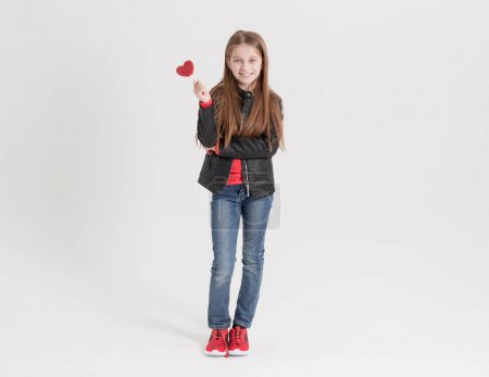 Girl teenager keeps heart shaped lollipops