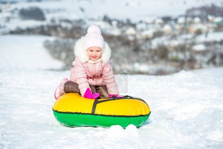 Little girl sits on snow tube