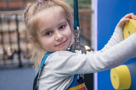 Portrait of teen girl on the climbing wall
