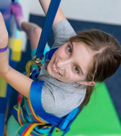 Photo pour Gros plan portrait de jeune fille sur le mur d'escalade dans le centre de divertissement - image libre de droit