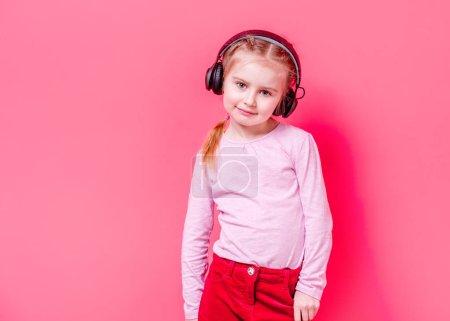Photo pour Petite fille moderne posant dans des écouteurs sur fond rose - image libre de droit
