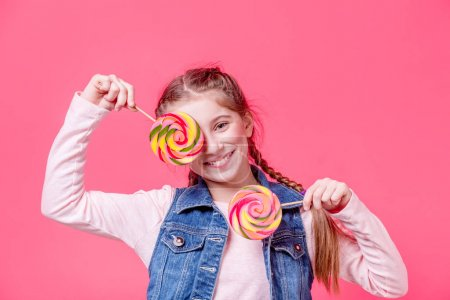 Photo for Cheerful teenage girl cover her eyes with two round lollipops over pink background - Royalty Free Image
