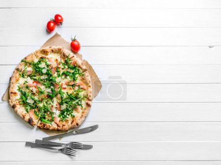 Photo for Itallian homemade pizza served on white wooden background with cutlery and cherry tomatoes. Copyspace, top view - Royalty Free Image
