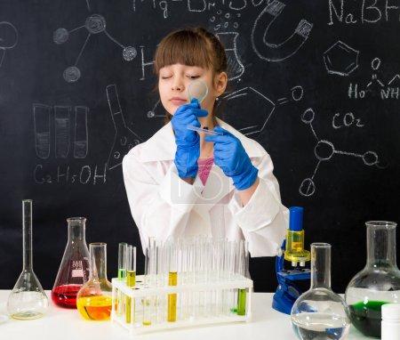 Photo pour Petite écolière en robe blanche regardant à travers loupe sur réactifs en laboratoire de chimie - image libre de droit