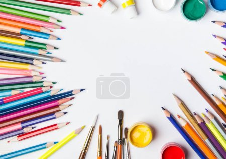 Top view of paint brushes, color pencils and watercolors