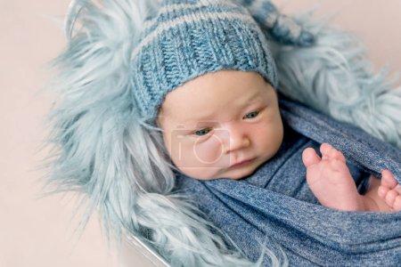 Bebé recién nacido acostado en un bebedero con una manta azul