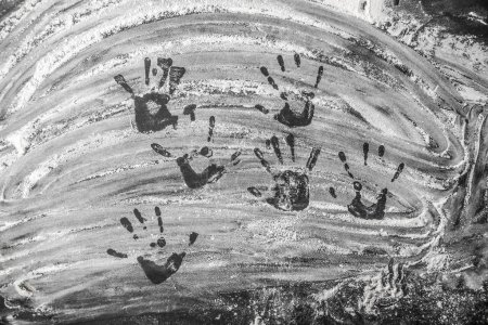 Photo pour Farine de cuisson blanche sur fond d'ardoise noire avec des traces de mains d'enfants vue du dessus - image libre de droit