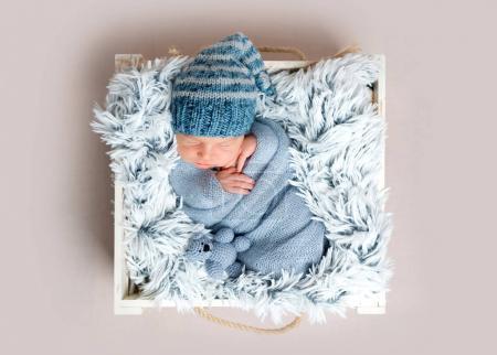 Recién nacido durmiendo en caja entre mantas azules