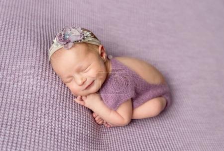 Little newborn baby girl in purple bodysuit smiling while sleeping
