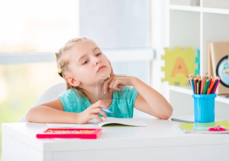 Photo for Focused little girl studying in classroom - Royalty Free Image