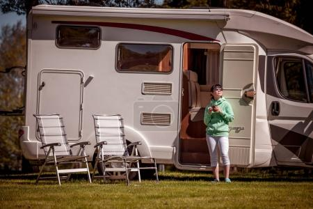 Photo for Woman is standing with a mug of coffee near the camper. Caravan car Vacation. Family vacation travel, holiday trip in motorhome RV - Royalty Free Image