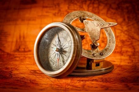 Photo for Vintage still life. Vintage compass lies on an ancient world map in 1565. - Royalty Free Image