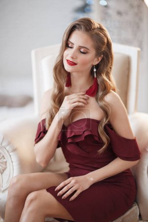 Photo for Beautiful sexy lady in an elegant burgundy dress. Close up fashion portrait of model indoors. Beauty brunette woman. Attractive woman in an open dress, posing alone, sitting in a posh white armchair in a room - Royalty Free Image