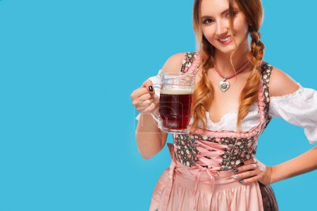 Photo for Half-length portrait of young sexy blonde with big breast wearing color dirndl with white blouse holding the beer mug Isolated on orange background - Royalty Free Image