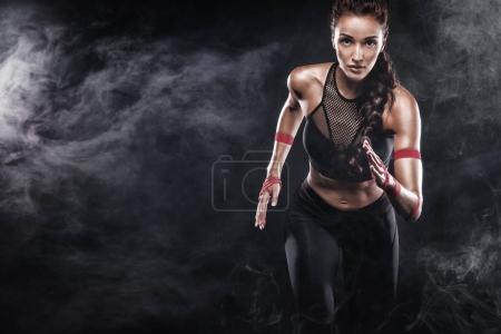 Foto de Un atlético fuerte, corredor femenino en el bacground negro usando un equipo apretado, de la aptitud. - Imagen libre de derechos