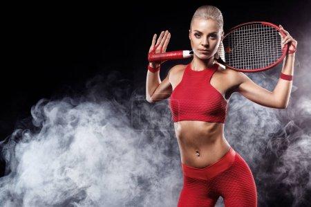 Photo pour Belle fille joueuse de tennis avec une raquette sur fond sombre avec des lumières - image libre de droit