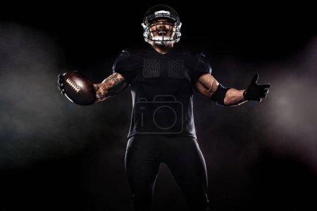 Photo pour Joueur de football américain isolé sur fond noir - image libre de droit