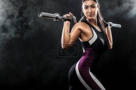 Sporty belle femme avec haltère fait de l'exercice de fitness à fond noir pour rester en forme