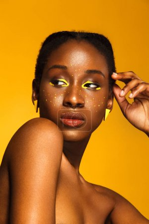 Photo for Cheerful young african woman with yellow makeup on her eyes. Female model laughing against orange background. - Royalty Free Image