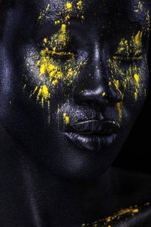 fröhliche junge Afrikanerin mit Kunst-Mode-Make-up. eine erstaunliche Frau mit schwarzem Make-up und undichter gelber Farbe