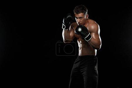 Photo pour Street fighter combats en gants de boxe. Isolé sur un fond noir avec copie de l'espace. Photo d'action. Concept sportif. - image libre de droit