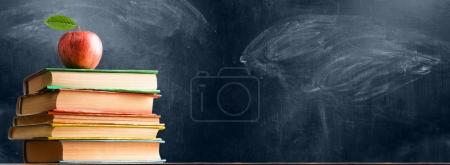 Photo for School accessories, books and fresh apple against chalkboard - Royalty Free Image