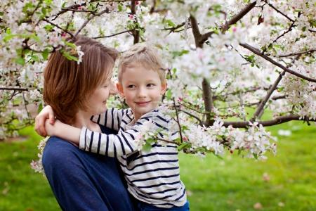 Photo for Loving young mother and her little son enjoying time together and blooming spring trees, mother's day concept - Royalty Free Image