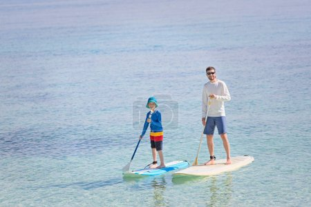 Photo for Family of two, little boy and young father, enjoying stand up paddleboarding together at fiji, active family vacation concept - Royalty Free Image