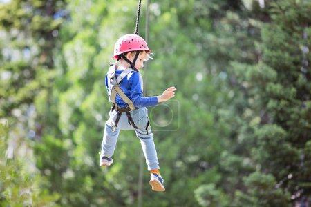 smiling little boy ziplining in treetop adventure park, healthy active lifestyle concept