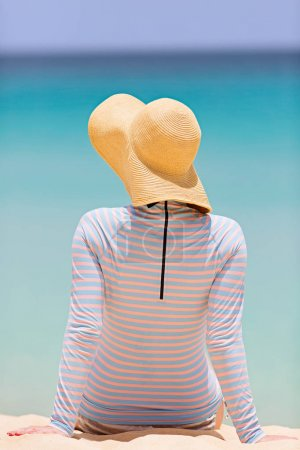 back view of woman in sunhat and rashguard enjoying summer beach vacation, sun protection concept
