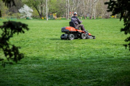 Workers mow the grass