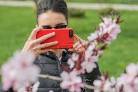 Girl takes pictures of nature and flowers