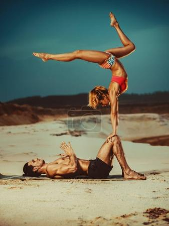 Sports couple doing acroyoga exercises