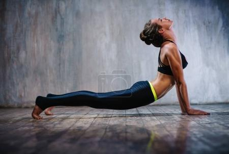 Photo for Young slim sports woman stretching on stone wall background - Royalty Free Image