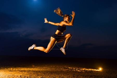 Photo for Young sports woman high jumping outdoors twilight training - Royalty Free Image