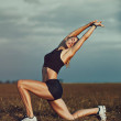 Young slim sports woman stretching on summer field...