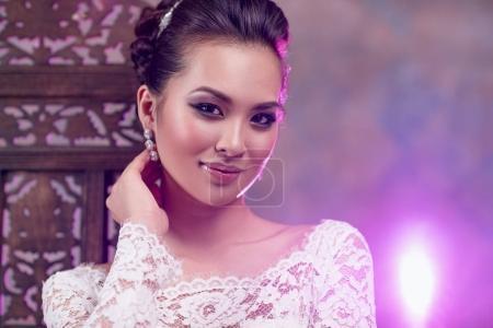 Photo pour Jeune femme asiatique en robe blanche portrait de mode avec une lumière rose vif sur le fond - image libre de droit