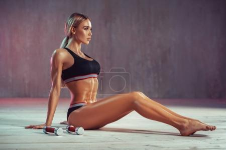 Photo for Young sexy blond fitness woman sitting on floor with two small dumbbells. Soft pink colors. - Royalty Free Image