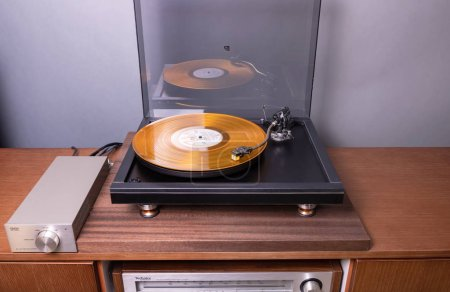 Photo for Vintage Stereo Turntable Plays Yellow Vinyl Record Album - Royalty Free Image