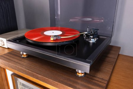Photo for Vintage Stereo Turntable Plays Red Vinyl Record Album, angled view - Royalty Free Image