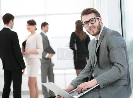 closeup of businessman with laptop on his knees on the backgroun