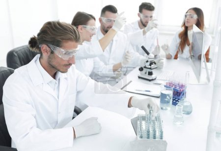 Scientists working with a microscope and make notes in the workplace