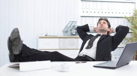 businessman relaxes sitting behind a Desk