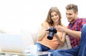happy young couple checks photos on photos the camera